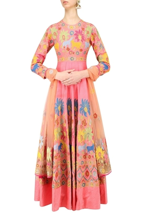 a pink anarkali kurta in blended cotton silk base with with colorful aari work all over with round neck and key hole back. It comes along with an orange dupatta in net with floral aari embroidery and has pink borders and hanging tassels.