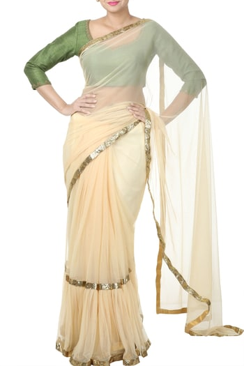 Green Zardozi Embroidery Blouse With Beige Saree #thehlabel #GreenZardozi #EmbroideryBlouse #BeigeSaree #Green #Zardozi #Embroidery #Blouse #Saree    Flaunt your trendy side wearing this beige net saree with gathers in pleats and lampi border. It is paired with green raw silk blouse that has zardosi embroidery and net sleeves.
