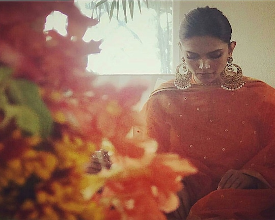 Continuing the series on our celebrity brides, we are now moving onto the absolutely gorgeous Deepika Padukone, who is the newest entrant into the world of matrimony. As someone who is extremely rooted in her traditions and family values, Deepika Padukone knew that she wanted all the traditions to be followed. So, before she would exchange her vows with fellow Bollywood celebrity Ranveer Singh, she chose to have a traditional pooja. For this pooja, she chose to look simple and wore an orange kurta with a cream coloured churidar. She matched the outfit with an orange coloured dupatta with a gold border and a small gold print all over.  Like her contemporary Anushka Sharma, Deepika also chose Italy as her wedding destination and kicked things off with a mehendi ceremony. The light pink of her outfit matched the rosy hue that the bride to be had on her face. The outfit had embroidery in the same colour, making the outfit look simple, yet elegant. The edges of the dupatta had a darker shade of pink, and Deepika chose to team it with a similar coloured woollen stole.  For another one of her pre-wedding ceremonies, Deepika chose to go with an off tissue saree in pale gold, over which she wore a dupatta of the same colour and material. She teamed the same with traditional kundan work jewellery and the jasmine garland on her hair bun, completed the south Indian look for her!  Because Deepika is from Karnataka, specifically the Konkan region of Karnataka and Ranveer comes from a Punjabi hertage, there were two types of weddings – one south Indian, and one north Indian. For her south Indian style wedding, Deepika was the quintessential south Indian bride, resplendent in a deep red Kancheepuram saree and designer Sabyasachi gave her a veil in tissue, which also had a gold brocade border. The traditional jewellery and the jasmine flowers on her hair made her look gorgeous!  For her Punjabi style wedding, she was yet again traditional, but this time she was a traditionally Punja