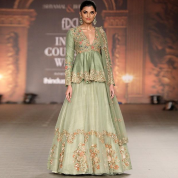 A stylish muted olive Peplum jacket embroidered with beautiful resham aari & water colour sequins, teamed with a sheer organza lehenga.