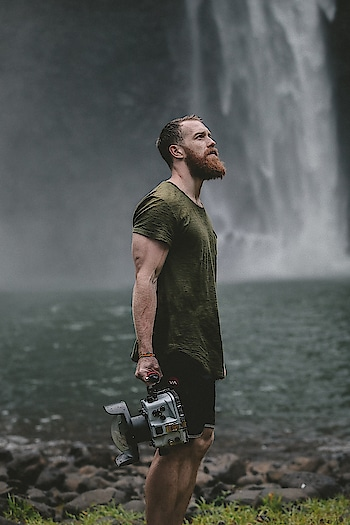 Videographer carrying a camera near a waterfall