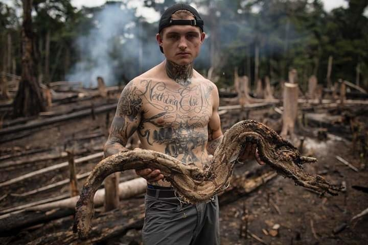 Photo @tbfrost | When forests are cut and burned, slow-moving creatures, especially reptiles, often are caught in the fires and burned alive. In this photo @harry__turner is holding the remains of an 8-foot red tail boa constrictor we found on the edge of a forest that had been in flames just days before. Smoke was rising from the earth and the ground was still hot to the touch. There was no color, just black and grey. The scene suggested the snake had slithered as fast as possible to make it to the river, but that the burns to over half its body overwhelmed it, and the beautiful creature died just a few feet from safety. The sadness amongst us was such that one could feel it in the air. The hardest part wasn't that they died but how they died. In one hour of searching a football field-sized clearing, @harry__turner, @melissalesh, and I found 4 dead snakes, 4 dead yellow footed tortoises, dozens of lizards and rodents, and hundreds of insects. The loss of rainforest alone gives all of us, including me, good reason to think more carefully about the sources of the things we buy. But knowing so many animals meet their end like this has renewed my vigilance to be a more careful consumer.  Head on over to @tbfrost to see a happier photograph of this same species of boa alive and well, living in a national park. #snakes #snakesofinstagram #rainforest #peru #snek #fires #deforestation #reptiles